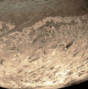 Rastros oscuros en el polo sur de Tritón. Probablemente, depósitos de partículas de antiguas erupciones de nitrógeno