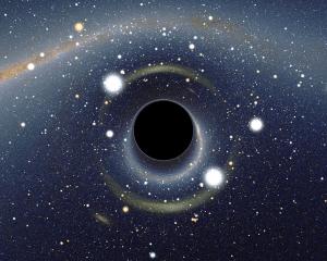 """Esto es una simulación de un agujero negro frente a la Gran Nube de Magallanes. Crédito: Usuario """"Alain r"""" de Wikipedia."""